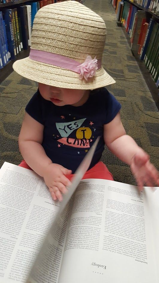Picture of a cute baby in a hat reading a book on Ecology